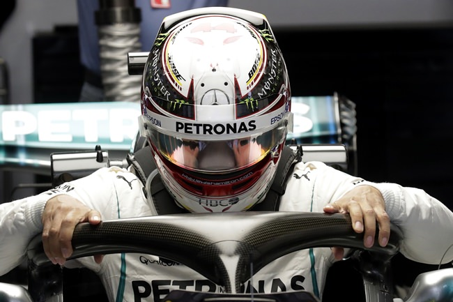 Mercedes driver Lewis Hamilton of Britain gets into his car during the first practice session for the Chinese Formula One Grand Prix at the Shanghai International Circuit in Shanghai, Friday, April 13. (AP Photo/Andy Wong)
