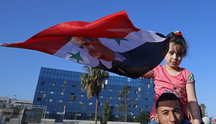 A Syrian girl holds up a Syrian national flag with a picture of President Bashar Assad as government supporters chant slogans against U.S. President Trump during demonstrations following a wave of U.S., British and French military strikes to punish Assad for suspected chemical attack against civilians, in Damascus, Syria, Saturday, April 14, 2018. (AP Photo/Hassan Ammar)