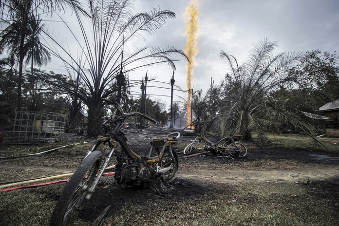 Burnt-out motorbikes are seen near a burning oil well after it caught fire in Pasir Putih village in eastern Aceh, Indonesia, Wednesday, April 25. (AP Photo/Zik Maulana)