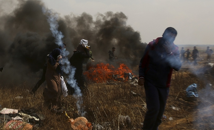 Palestinian protesters run to cover from tear gas fired by the Israeli troops during a protest at the Gaza Strip's border with Israel, east of Khan Younis, Friday, April 27. (AP Photo/Adel Hana)