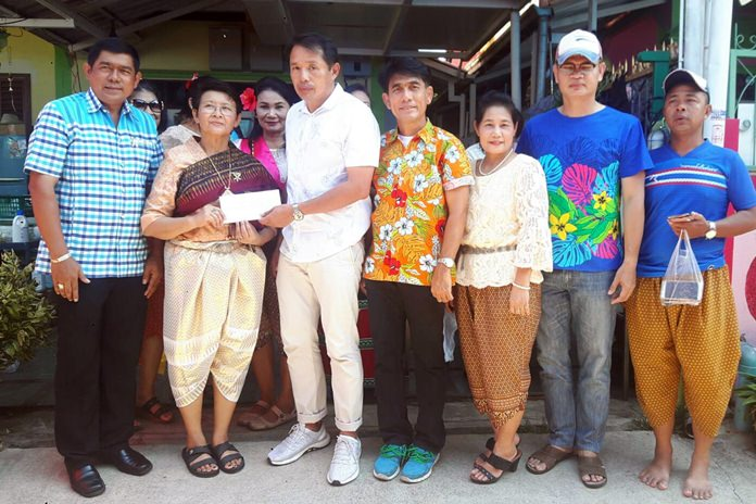 Marbpradu Community President Supaporn Sanphakaew accepts a donation from the local We Love Chonburi-Pattaya Group.