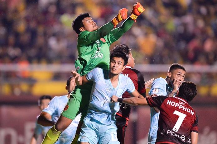 Tero goalkeeper Nont Muangngam punches the ball clear as he is challenged by Pattaya United's Chayawat Srinawong (13) during the first half of a Thai League 1 fixture between Pattaya United and Police Tero at the Boonyachinda Stadium in Bangkok, Sunday, April 29. (Photo courtesy Pattaya United FC)