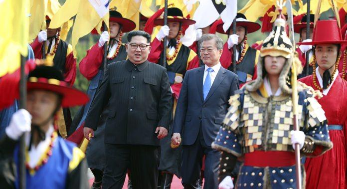 North Korean leader Kim Jong Un, left, and South Korean President Moon Jae-in, right, walk together through an honor guard at the border village of Panmunjom. (Korea Summit Press Pool via AP, File)