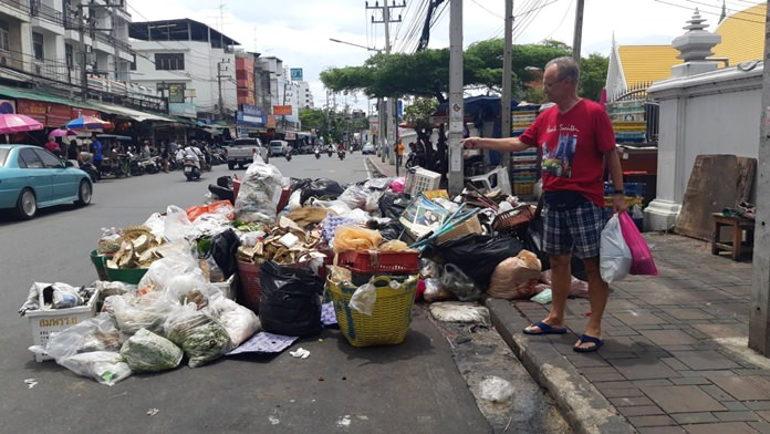 A foreign visitor points at the huge pile of garbage in front of Wat Chai Mongkol.