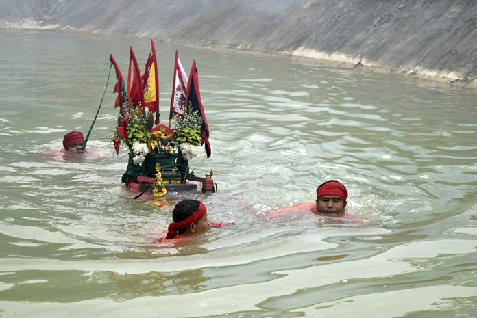 Devotees perform the ritual of bearing the image of Mae Lim Kor Niew through deep water.