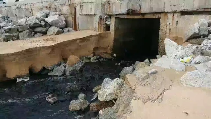Black and smelly sewage flows out from under the Jomtien Beach Road into the sea.