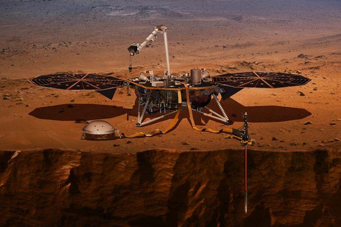 This illustration shows the InSight lander drilling into Mars. (NASA via AP)