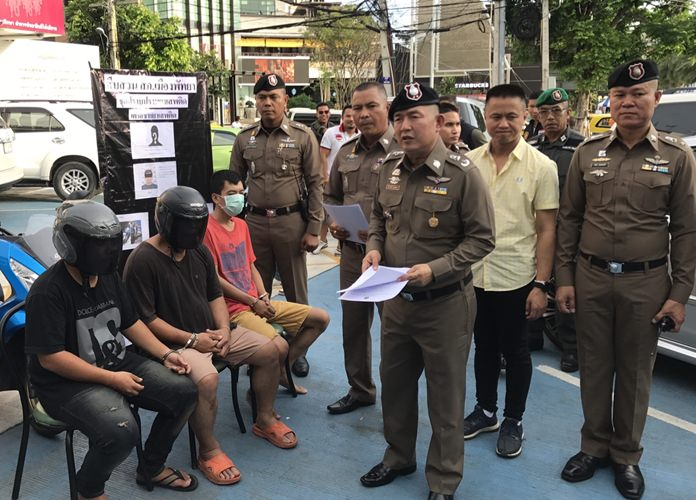 Ex-cop Vichai Kradkrayang and his accomplices sit at a news conference under the watchful eyes of Pol. Maj. Gen. Nantachart Supamongkol and Pol. Col. Appichai Kroppech.