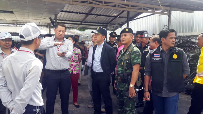 District Chief Naris Niramaiwong leads a team to inspect the offending paint factory.
