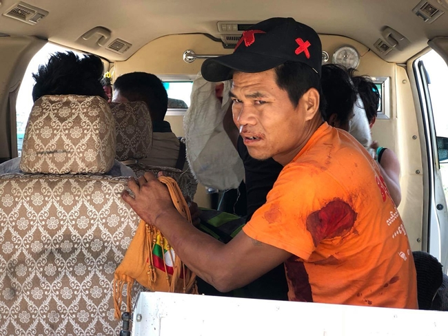 An injured man sits inside a vehicle in Muse, northern Shan state, Myanmar Saturday, May 12. (Thaung Tu via AP)