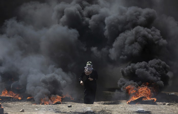 A Palestinian woman walks through black smoke from burning tires during a protest on the Gaza Strip's border with Israel, Monday, May 14. (AP Photo/Khalil Hamra)