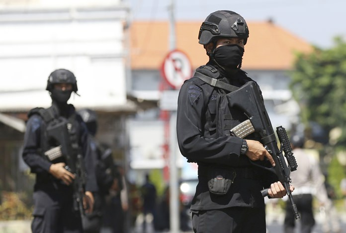 Officers stand guard outside the local police headquarters following an attack in Surabaya, East Java, Indonesia, Monday, May 14. (AP Photo/Achmad Ibrahim)