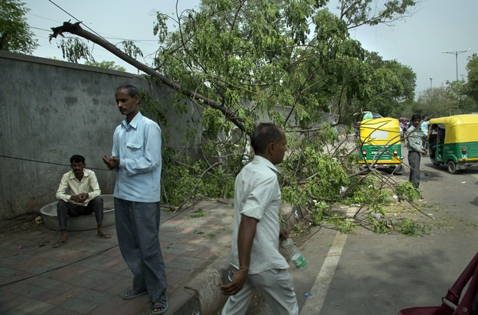 Commuters walk past an uprooted tree in New Delhi, India, Monday, May 14. (AP Photo/Manish Swarup)
