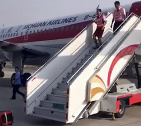 Ground crew are seen leaving the Sichuan Airline flight that made an emergency landing in Chengdu in southwestern China's Sichuan province, Monday, May 16. (AP Photo)