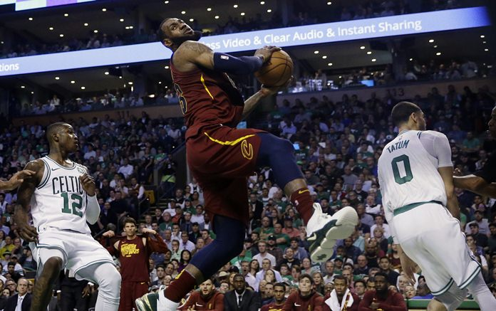 Cleveland Cavaliers forward LeBron James, center, recoils after colliding with Boston Celtics forward Jayson Tatum, right, in front of Celtics guard Terry Rozier, left, during Game 2 of the NBA basketball Eastern Conference finals Tuesday, May 15, in Boston. (AP Photo/Charles Krupa)