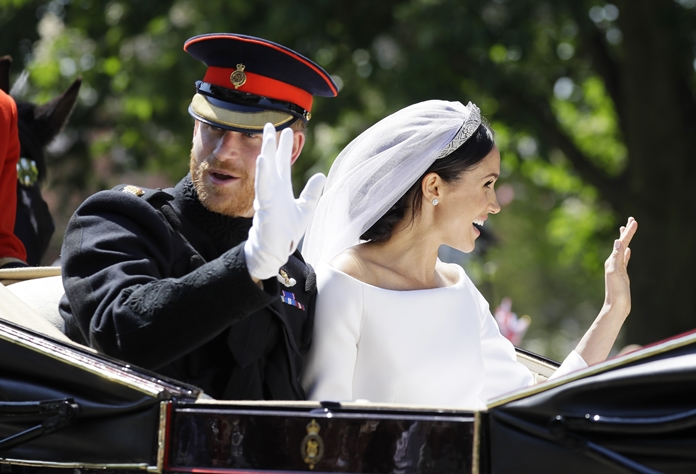 Britain's Prince Harry, left, and Meghan Markle wave from a carriage after their wedding ceremony at St. George's Chapel in Windsor Castle, near London, Saturday, May 19. (AP Photo/Kirsty Wigglesworth, pool)