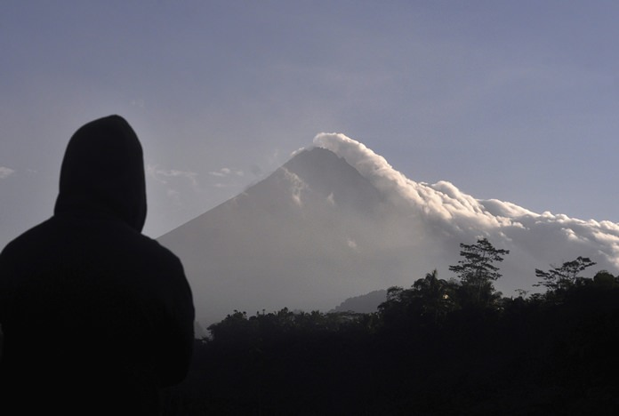 A man watches as Mount Merapi spews volcanic smoke in Yogyakarta, Indonesia, Tuesday, May 22. (AP Photo/Slamet Riyadi)