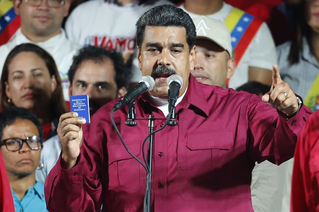 Venezuela's President Nicolas Maduro, holding a copy of the country's constitution, addresses supporters at the presidential palace in Caracas, Venezuela, after electoral officials declared he was re-elected on Sunday, May 20. (AP Photo/Ariana Cubillos)