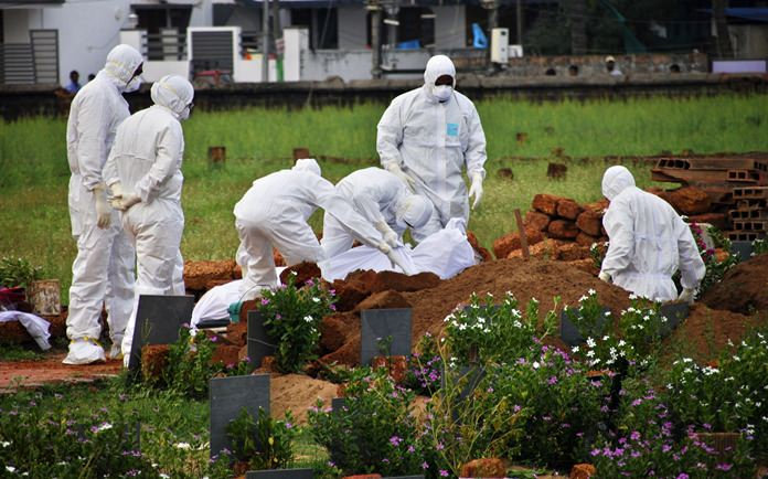 In this Thursday, May 24, photo, paramedics wear protective suits as a precautionary measure against the Nipah virus as they bury a body in Kozhikode, Kerala, southern India. (AP Photo/K.Shijith)