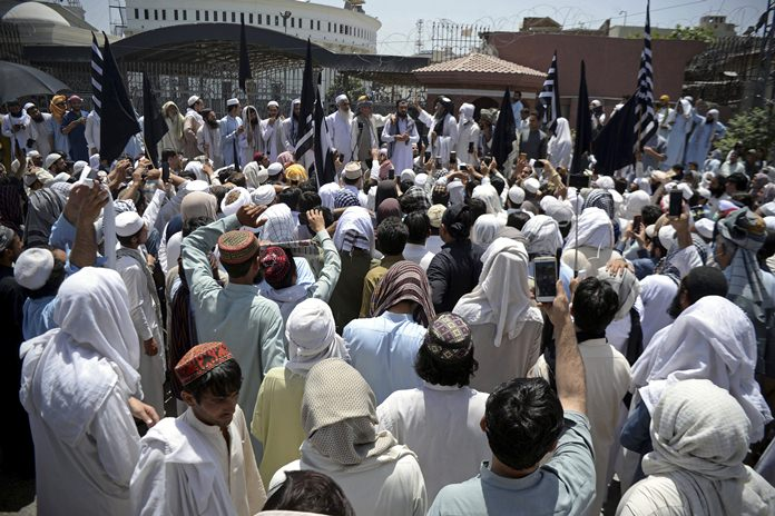 Supporters of the hard-line religious party, Jamiat Ulema Islam, protest at the main entrance of the provincial assembly in Peshawar, Pakistan, Sunday, May 27. (AP Photo/Mohammad Sajjad)