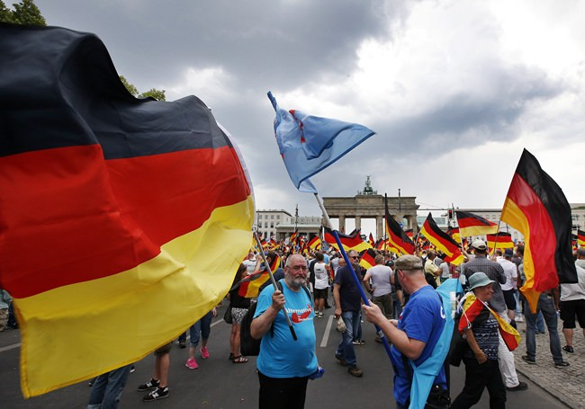 Supporters of German AfD wave flags in front of the Brandenburg Gate in Berlin, Germany, Sunday, May 27. (AP Photo/Michael Sohn)