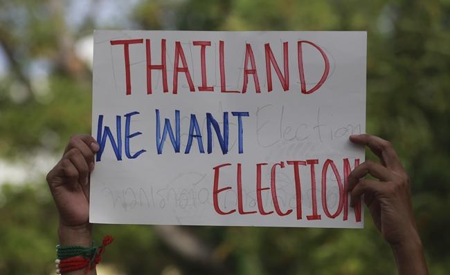 A pro-democracy demonstrator holds a poster in Bangkok, Saturday, May 5. (AP Photo/Sakchai Lalit)