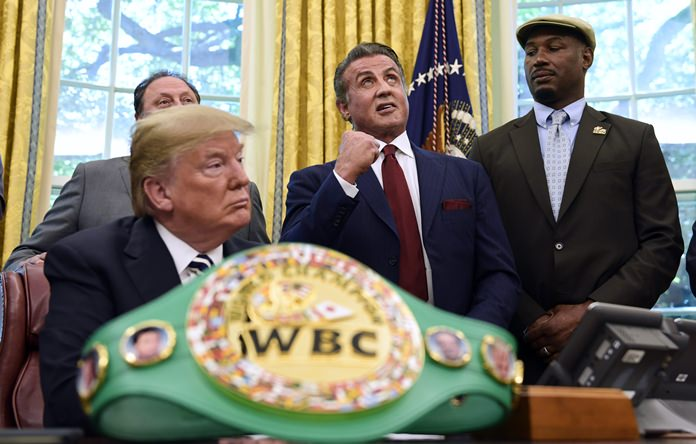 In this May 24, 2018 photo, President Donald Trump (left) and heavyweight boxer Lennox Lewis (right) watch as Sylvester Stallone gestures in the Oval Office of the White House in Washington. (AP Photo/Susan Walsh)