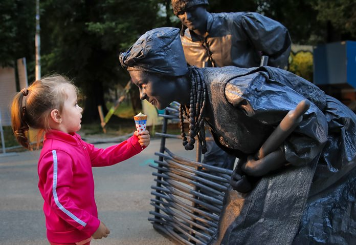 In this Thursday, May 24, photograph, a child offers ice-cream to artists of Ukraine's Artel Myth theatre at the Living Statues International Festival, in Bucharest, Romania. (AP Photo/Vadim Ghirda)