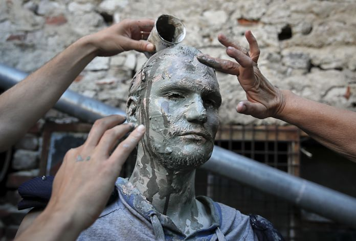 An artist of Romania's Masca theatre has make-up applied to his face before performing at the Living Statues International Festival, in Bucharest. (AP Photo/Vadim Ghirda)
