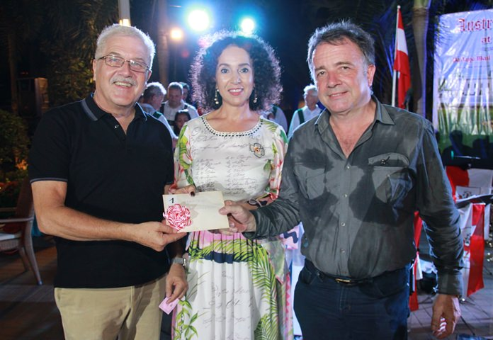 Anselma (centre) smiles as Thomas Sack (right) presents the prize of a helicopter flight to the lucky winner.