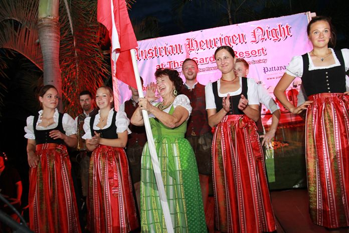 Elfi Seitz holding the Austrian flag shouts out a traditional yodel, supported by the 'Silberplattler' dancers.