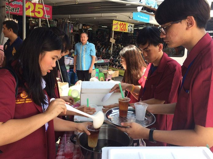 "Thammasat University students hand out food and cold drinks as part of the school's ""New Era Kids"" project."