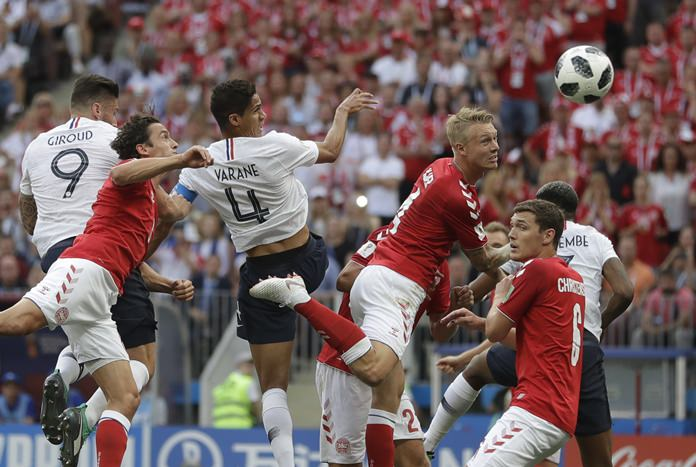 Denmark's Simon Kjaer, top centre right, heads the ball under pressure from France's Raphael Varane top center left, during the group C match between Denmark and France at the 2018 soccer World Cup at the Luzhniki Stadium in Moscow, Russia, Tuesday, June 26. (AP Photo/Matthias Schrader)