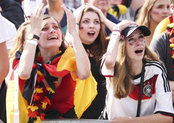 Soccer fans react after Germany was eliminated from the World Cup as they watch the group F World Cup match between South Korea and Germany during an event in Hamburg, northern Germany, Wednesday, June 27, 2018. (Ulrich Perrey/dpa via AP)