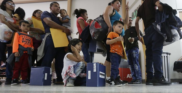Immigrant families seeking asylum wait in line at the central bus station after they were processed and released by U.S. Customs and Border Protection, Friday, June 29, in McAllen, Texas. (AP Photo/Eric Gay)