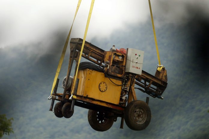 A military transport helicopter carries a drill machine to be used for the rescue search of missing 12 boys and their soccer coach, in Mae Sai, Chiang Rai province, in northern Thailand, Monday, July 2, 2018. (AP Photo/Sakchai Lalit)