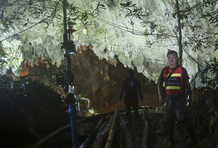 A rescuer stands in front of the entrance to the flooded cave complex in Mae Sai, Chiang Rai province, Sunday, July 1. (AP Photo/Sakchai Lalit)