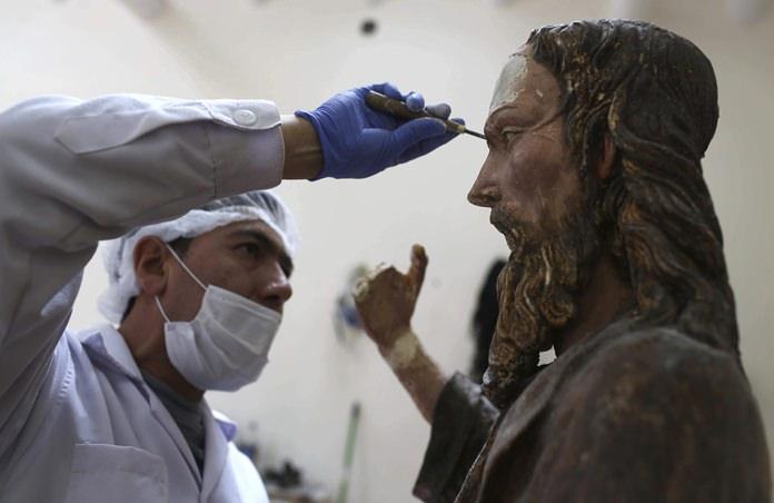 An art restorer works on a sculpture of Jesus Christ in a studio of the Ministry of Culture's Restoration Center in Cuzco, Peru. (AP Photo/Martin Mejia)