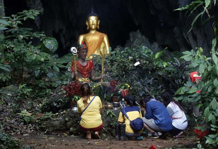 Family members pray in front of a Buddhist statue near the cave. (AP Photo/Sakchai Lalit)