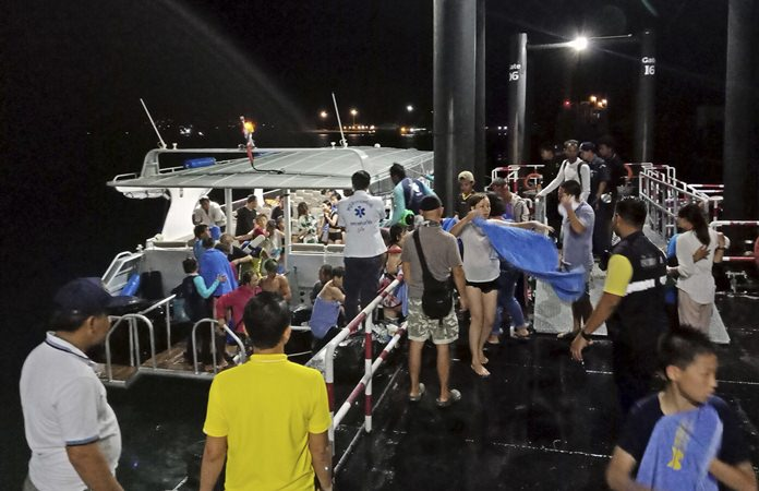 Rescued tourists from a boat carrying dozens of Chinese tourists that overturned in rough seas and sank off southern Thailand are helped onto a pier Thursday, July 5, in Phuket. (Thailand Royal Police via AP)
