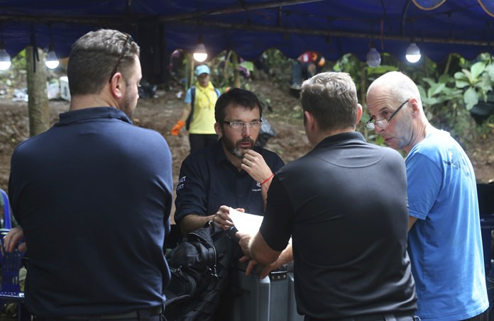 Australian Federal Police and Defense Force personnel on Thursday, July 5, talk about extraction plans to get the 12 boys and their soccer coach out of the flooded cave. (AP Photo/Sakchai Lalit, File)