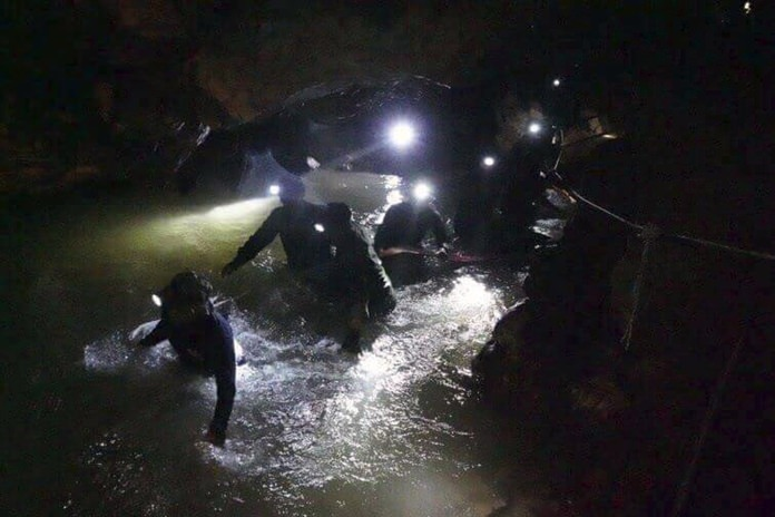 Thai rescue teams walk through rushing water inside the cave complex July 2. (Tham Luang Rescue Operation Center via AP, File)