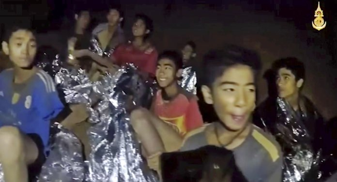 In this July 3, 2018, image taken from video provided by the Royal Thai Navy Facebook Page, the boys smile as a Thai Navy SEAL medic helps the injured shortly after they were found. (Royal Thai Navy Facebook Page via AP)