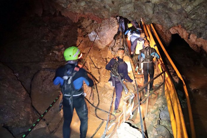 Thai rescue team members walk inside the cave where 12 boys and their soccer coach were trapped for 18 days. (Royal Thai Navy via AP)