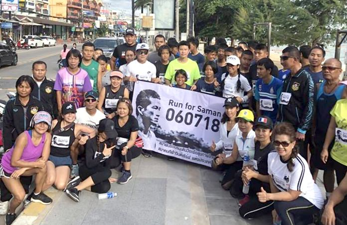 Run-walk participants pose with an appeal banner for the family of deceased Navy SEAL Saman Kunan on Jomtien Beach, Wednesday, July 11.