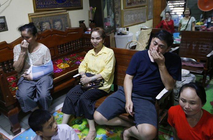 Banphot Konkum, the uncle of Duangpetch Promthep, one of the boys rescued from a flooded cave, second right, and other members of his family watch Duangpetch and the rest of the boys live on television at his home in Mae Sai district, Chiang Rai. (AP Photo/Sakchai Lalit)