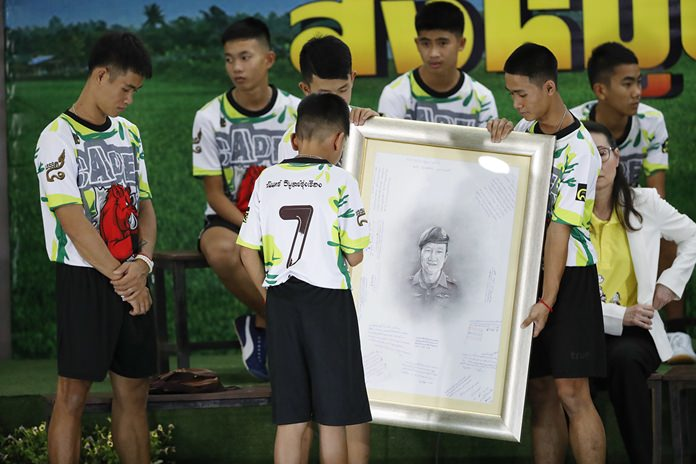 Coach Ekkapol Janthawong, left, and the 12 boys show their respect and thanks as they hold a portrait of Saman Gunan, the retired Thai SEAL diver who died during their rescue attempt. (AP Photo/Vincent Thian)