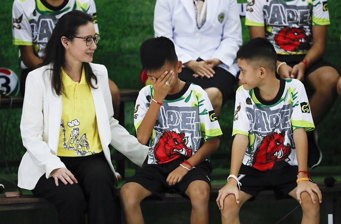 "Rescued soccer player ""Titan"" Chanin Vibulrungruang reacts after paying respect to a portrait of Saman Gunan. (AP Photo/Vincent Thian)"