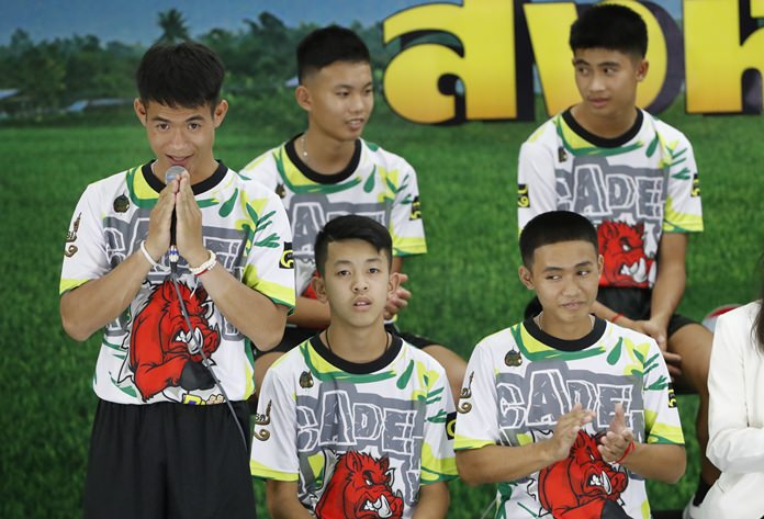 Coach Ekkapol Janthawong, left, and members of the rescued soccer team express their thanks during a press conference in Chiang Rai, Wednesday, July 18. (AP Photo/Vincent Thian)