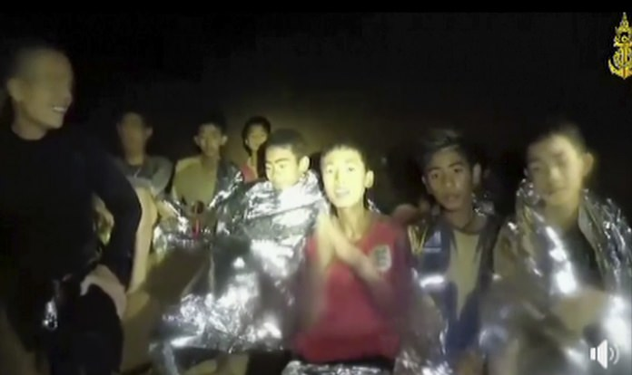 In this July 3, 2018, image taken from video provided by the Thai Navy Seal, Thai boys are with Navy SEALs inside the cave, Mae Sai, northern Thailand. With heavy rains forecast to worsen flooding in a cave in northern Thailand where 12 boys and their soccer coach are waiting to be extracted by rescuers, authorities say they might be forced to have them swim out through a narrow, underwater passage. The 13 are described as healthy and being looked after by medics inside the cave.(Thai Navy Seal via AP)